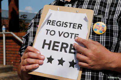 A man holds voter registration forms outside a campaign rally with U.S. Democratic presidential candidate Hillary Clinton in Greensboro, North Carolina, United States September 15, 2016.
