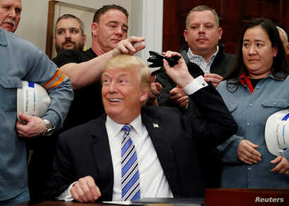 U.S. President Donald Trump gives out pens he used to sign presidential proclamations placing tariffs on steel and aluminum imports to workers from the steel and aluminum industries at the White House in Washington, March 8, 2018.