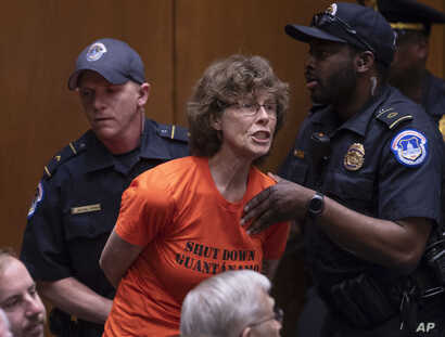 A protester is removed by Capitol Police officers as she shouts at Gina Haspel, President Donald Trump's pick to lead the Central Intelligence Agency, at her confirmation hearing before the Senate Intelligence Committee, on Capitol Hill in Washington...