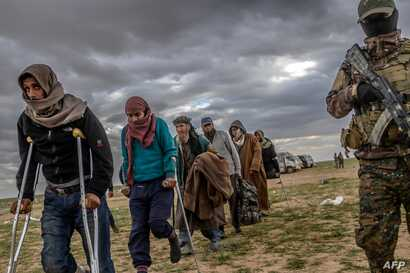 Men suspected of being Islamic State fighters wait to be searched by members of the Kurdish-led Syrian Democratic Forces (SDF) after leaving the IS group's last holdout of Baghuz, in Syria's northern Deir Ezzor province, Feb. 27, 2019.