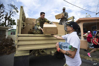 FILE - Soldiers and National Guardsmen organize aid for the Santa Ana community in the aftermath of Hurricane Maria in Guayama, Puerto Rico, Oct. 5, 2017.