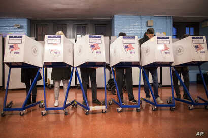 Voters fill out their forms at a polling station in the Brooklyn borough of New York, Nov. 8, 2016.