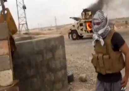 This image from video posted by Iraqi Revolution, a group supporting ISIL, shows a militant standing in front of a burning Iraqi Army Humvee in Tikrit, Iraq, June 11, 2014.