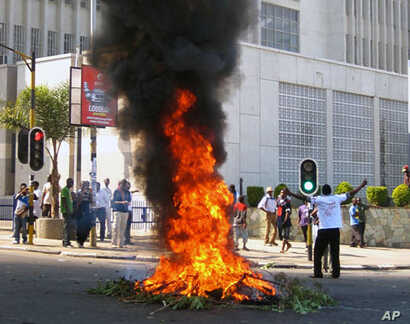 A protester burns vegetation in a street in Lilongwe, Malawi, Wednesday, July 20, 2011