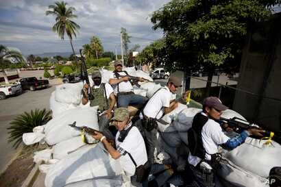 FILE - In this Jan. 12, 2014 file photo, men belonging to the Self-Defense Council of Michoacan, ride on a sandbag-filled truck while trying to flush out alleged members of The Caballeros Templarios drug cartel from the town of Nueva Italia, Mexico.