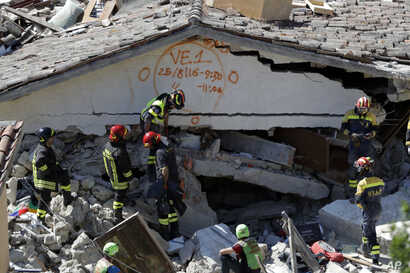 Rescuers mark a building with paint signaling the date and time of start and end of the search operation on that building, following Wednesday's earthquake in Pescara Del Tronto, Italy, Aug. 25, 2016.