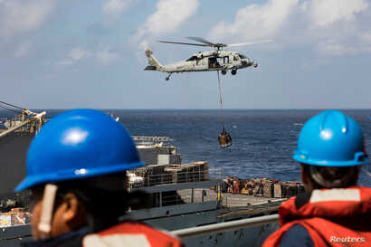 Sailors aboard the amphibious assault ship USS Kearsarge (LHD 3) observe as an MH-60 Sea Hawk helicopter transfers pallets of supplies from the fast combat support ship USNS Supply (T-AOE 6) during replenishment-at-sea for continuing operations as pa...