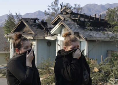 Crystal Shore, left, and her sister Carrie look over the damage to their neighbor's home along Via San Anselmo in the Sylmar area of Los Angeles, Dec. 6, 2017.