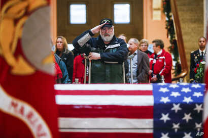 A mourner salutes the casket of John Glenn as he lies in honor in Columbus, Ohio.