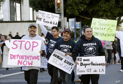 Immigration activists march in a rally against the U.S. Immigration and Customs Enforcement's (ICE) raids and deportation of immigrants near the downtown Los Angeles Federal Building, Jan. 26, 2016.