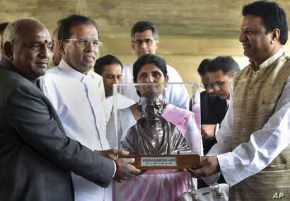 Sri Lankan President Maithripala Sirisena, second from left, and his wife Jayanthi Sirisena, second from right, receive a bust of Mahatma Gandhi during their visit to Rajghat, the memorial to the late Mahatma Gandhi, in New Delhi, India, Monday, Feb....