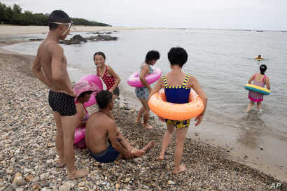 In this Aug. 20, 2018, photo, North Koreans enjoy the day on a seashore near Mount Chilbo, North Korea.