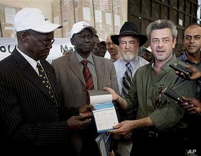 Eamon Omordha, right, Deputy Director of the UN Integrated Referendum and Electoral Division, hands over a referendum ballot to Justice Chan Reec Madut, left, Chairman of the Southern Sudan Referendum Bureau, during a material handover ceremony in Ju...