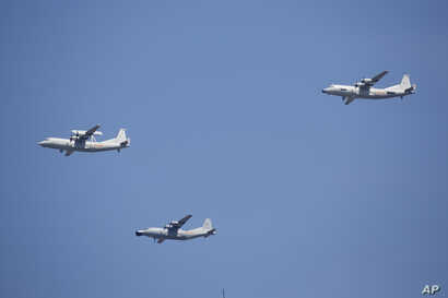 A KJ-200 airborne early warning and control plane, left, a Y-8J radar plane, center, and a Y-9JB radar plane, right, fly in formation during a parade commemorating the 70th anniversary of Japan's surrender during World War II in Beijing, Sept. 3, 201...