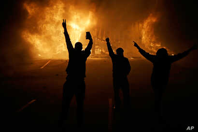In this Nov. 25, 2014 file photo, people watch as stores burn in Ferguson, Mo.