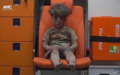 In this frame grab taken from video provided by the Syrian anti-government activist group Aleppo Media Center (AMC), a child sits in an ambulance after being pulled out or a building hit by an airstirke, in Aleppo, Syria, Aug. 17, 2016.