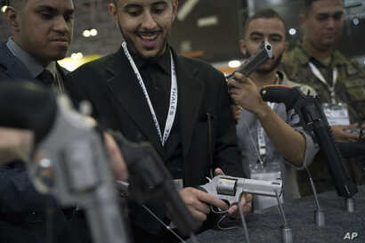 A man tries a revolver displayed at the LAAD Defense and Security International Exhibition in Rio de Janeiro, Brazil, April 2, 2019.