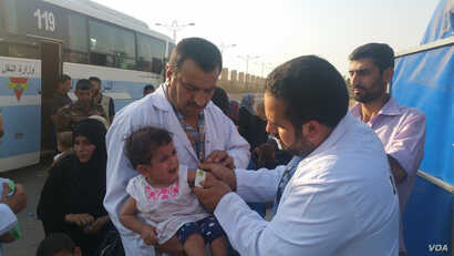 Medics at this collection point for fleeing families treat a baby for malnutrition, which they say is widespread among children in Mosul, Iraq, on July 12, 2017