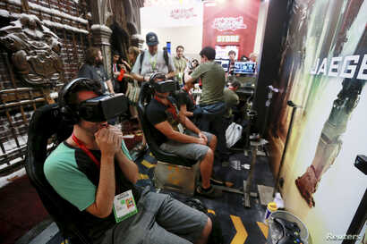 "Attendees wearing Oculus Rift virtual reality headsets view a 3-dimensional video for the ""Pacific Rim: Jaeger Pilot"" video game during the 2014 Comic-Con International Convention in San Diego, California, July 25, 2014."