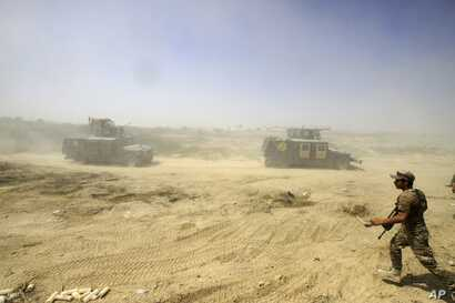 Iraqi security forces advance their positions during the fight against Islamic State militants in Fallujah, Iraq, June 15, 2016.