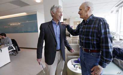 FILE - In this photo taken March 29, 2017, Dr. David Maloney of the Fred Hutchinson Cancer Research Center is greeted by patient Ken Shefveland, whose lymphoma was successfully treated with CAR-T cell therapy. A CAR-T cell treatment developed by Nova...