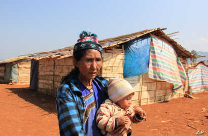 An ethnic Shan woman, who was displaced due to fighting between the Myanmar government army and ethnic Shan State Army North (SSA-N) on Oct. 6, 2015, stands in front of a camp for refugees with her grand daughter in Hai Pa village, northeastern Shan ...