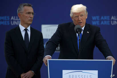 NATO Secretary General Jens Stoltenberg listens as President Donald Trump speaks during a ceremony to unveil artifacts from the World Trade Center and Berlin Wall for the new NATO headquarters in Brussels, May 25, 2017.