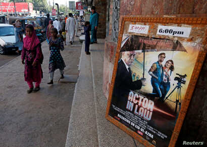 An advertising poster for a Pakistani film with Indian actors is seen outside a movie theater in Karachi, Pakistan, Sept. 30, 2016.