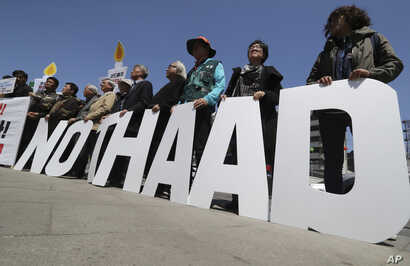"""Protesters hold letters reading """"NO THAAD"""" during a rally to oppose a plan to deploy an advanced U.S. missile defense system called Terminal High-Altitude Area Defense, or THAAD, near U.S. Embassy in Seoul, South Korea, April 26, 2017."""