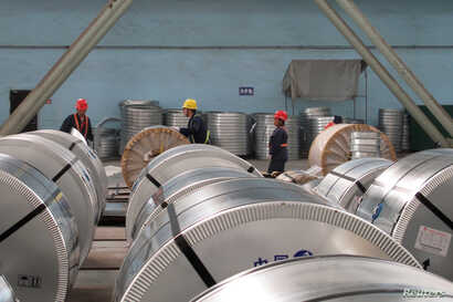 FILE - Workers pack cold rolled steel coil at a steel company in Zhangjiagang, Jiangsu province, China, April 27, 2018.