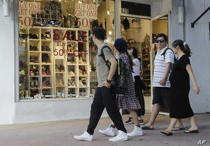 FILE - People walk past a shoe store at Lincoln Road Mall in Miami Beach, Fla., Feb. 3, 2016. A University of Michigan survey's measure of current economic conditions, released Jan. 18, 2019, decreased to 110.0 from a reading of 116.1 in December 20...