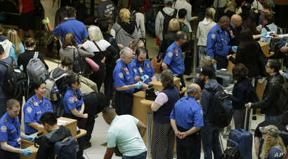 TSA agents check passenger boarding passes and identification at a security screening checkpoint, Thursday, May 19, 2016, at Seattle-Tacoma International Airport in Seattle.