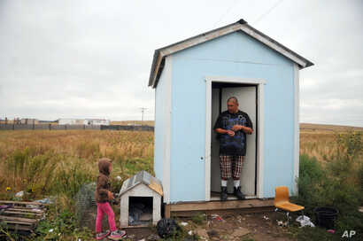 In this Wednesday, Sept. 30, 2015, photo, Raymond Eagle Hawk, right, stands in the doorway of his home that he shares with his daughter, Kimimila Eagle Hawk, left, and his girlfriend in Wounded Knee, S.D., on the Pine Ridge Indian Reservation.