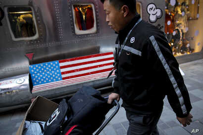 A delivery worker pushes a cart loaded with goods past by a bench with an American flag outside a fashion boutique selling U.S. brand clothing at the capital city's popular shopping mall in Beijing, Feb. 1, 2019.