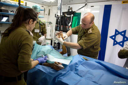 FILE - Members of the Israeli military medical team treat a Syrian man, who was injured in Syria's ongoing civil war, at a military hospital in the Israeli-occupied Golan Heights, close to the ceasefire line between Israel and Syria on February 18, 2...