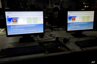 FILE - A computer user sits near displays with a message from the Chinese police on the proper use of the internet at an internet cafe in Beijing, China, Aug. 19, 2013.