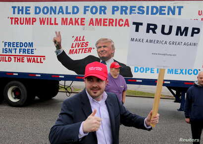 Bob Bolus, a supporter of U.S. Republican presidential candidate Donald Trump, gives the thumbs up to drivers as they pass by on Super Tuesday in Middleburg Heights, Ohio, March 15, 2016.
