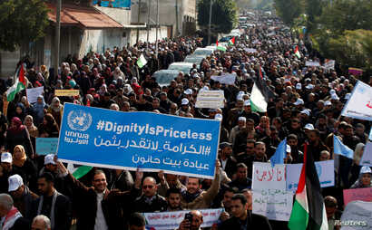 Palestinian employees of the United Nations Relief and Works Agency (UNRWA) hold signs during a protest against a U.S. decision to cut aid, in Gaza City, Jan. 29, 2018.