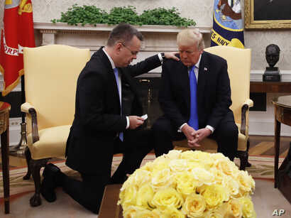 President Donald Trump prays with American Pastor Andrew Brunson in the Oval Office of the White House, Oct. 13, 2018, in Washington. Brunson returned to the U.S. after he was freed Friday, having been detained for nearly two years in Turkey.