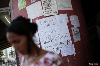 A woman walks past placards with prices of different products and services in a street of Caracas, Venezuela, Jan. 28, 2019.