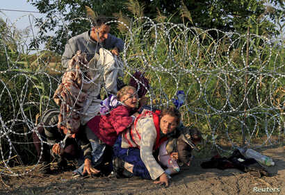 FILE - Syrian migrants cross under a fence into Hungary at the border with Serbia, near Roszke, August 2015.