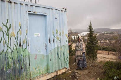 A Jewish settler covers herself from rain in Amona, an unauthorized Israeli outpost at the West Bank, east of the Palestinian town of Ramallah, Dec. 18, 2016.