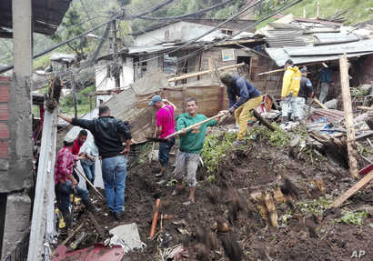 Residents work to unearth a house destroyed during a landslide in Manizales, Colombia, April 19, 2017.