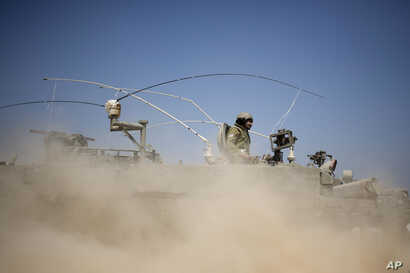 Israeli soldiers drive on an armored personal carrier near the Israel and Gaza Strip border, July 7, 2014.