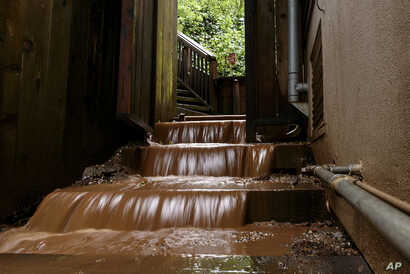 Water rushes down the stairs of a house near a mudslide that destroyed three homes on a hillside in Sausalito, Calif., Feb. 14, 2019.