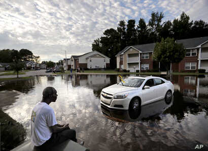 Augustin Dieudomme looks out at the flooded entrance to his apartment complex near the Cape Fear River as it continues to rise in the aftermath of Hurricane Florence in Fayetteville, N.C., Sept. 18, 2018.