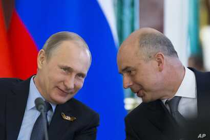 Russia's Finance Minister Anton Siluanov (R), seen in this May 8, 2015 photo with President Putin, on Thursday told Russian news agencies that Moscow is ready to consider Ukraine's debt proposals but warned that time is running out.
