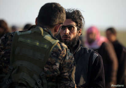 A fighter from Syrian Democratic Forces checks a man near the village of Baghuz, Deir Al Zor province, Syria Feb. 22, 2019.