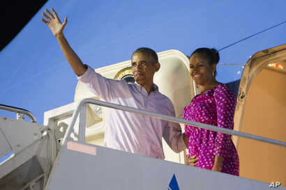 President Barack Obama, left, and first lady Michelle Obama wave as they board Air Force One to depart from Joint Base Pearl Harbor-Hickam at the end of their family vacation, Jan. 2, 2016, in Honolulu, Hawaii.