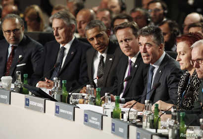 U.S. President Barack Obama, third from left, and British Prime Minister David Cameron, fourth from left, listen to NATO Secretary General Anders Fogh Rasmussen, third from right, as they participate in NATO Summit Session One, on Afghanistan and the...